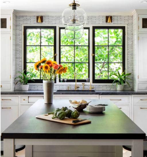 White Shaker cabinets and black granite countertops in a modern farmhouse kitchen