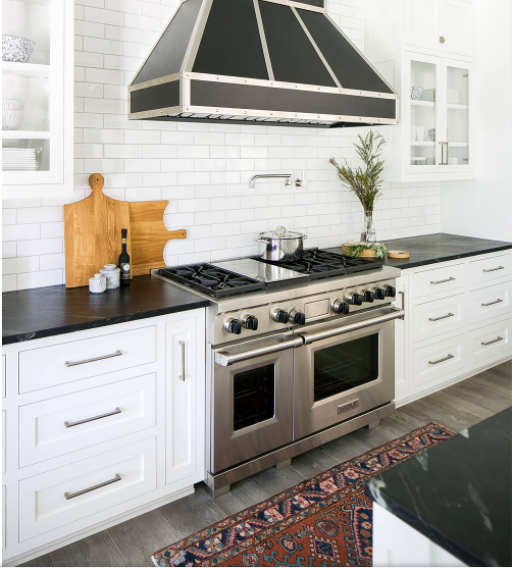 Modern kitchen with white shaker cabinets and black countertops