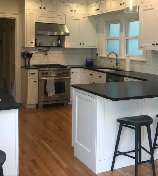 Traditional white Shaker cabinets and black countertops framed by natural wood floors