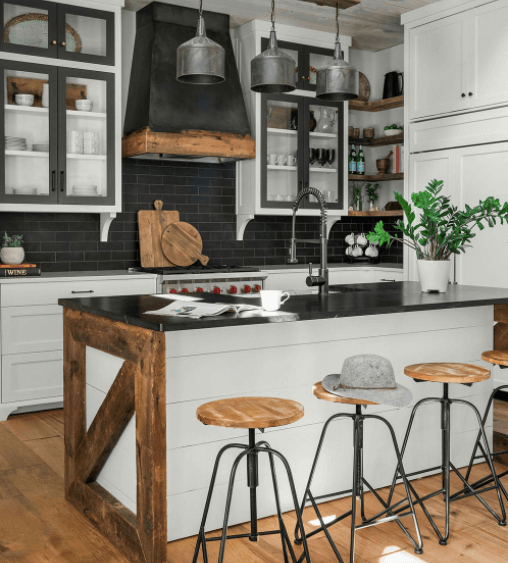 White cabinets and black countertops in a rustic farmhouse kitchen
